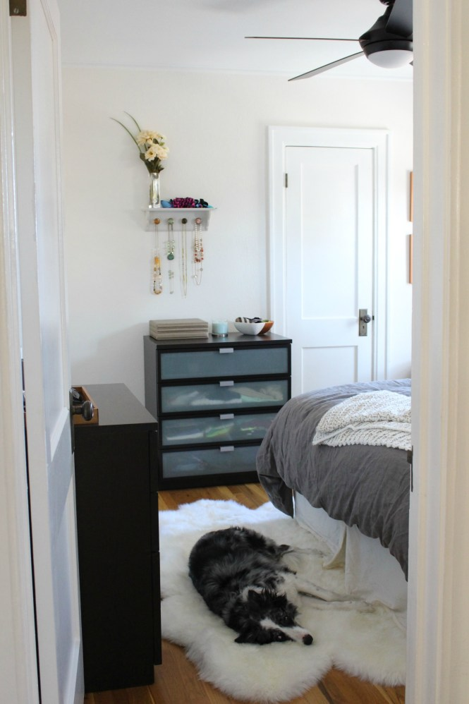 Cozy neutral bedroom reveal through door, dog on sheepskin rug