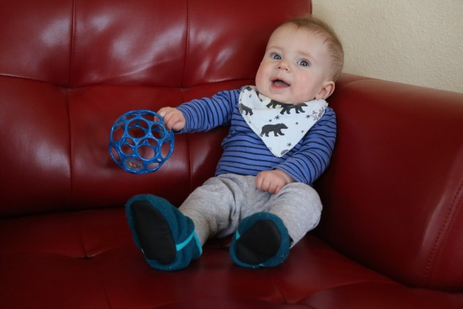 Henry sitting in the red chair playing with rattle
