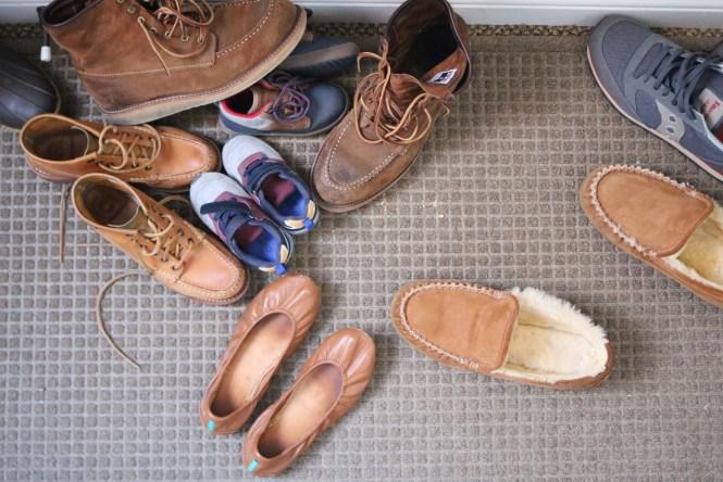 Shoes piled at narrow entry landing zone on waterhog mat