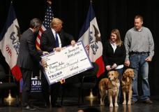 Republican presidential candidate Donald Trump distributes a check to Puppy Jake during a campaign event at the Adler Theater, Saturday, Jan. 30, 2016 in Davenport, Iowa. (AP Photo/Paul Sancya)