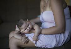 Gleyse Kelly da Silva holds her daughter Maria Giovanna as she sleeps in their house in Recife, Pernambuco state, Brazil, Wednesday, Jan. 27, 2016. Brazilian officials still say they believe there's a sharp increase in cases of microcephaly and strongly suspect the Zika virus, which first appeared in the country last year, is to blame. The concern is strong enough that the U.S. Centers for Disease Control and Prevention this month warned pregnant women to reconsider visits to areas where Zika is present. (AP Photo/Felipe Dana)