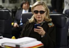 FILE - In this Oct. 18, 2011, file photo, then-Secretary of State Hillary Rodham Clinton checks her Blackberry from a desk inside a C-17 military plane upon her departure from Malta, in the Mediterranean Sea, bound for Tripoli, Libya. The private email server running in Clinton's home basement when she was secretary of state was connected to the Internet in ways that made it more vulnerable to hackers, according to data and documents reviewed by The Associated Press. (Kevin Lamarque/Pool Photo via AP, File)