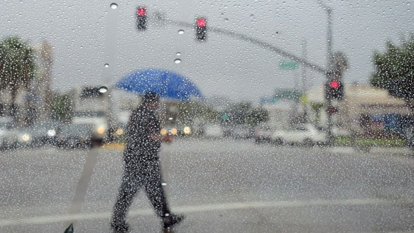 A man crosses a street during a steady rainfall on September 15, 2015 in Los Angeles, California, as a low-pressure system filled with moisture from a former tropical cyclone unleashed heavy rain. At least eight people were pulled into rain-swollen San Gabriel River Tuesday as a storm drenched Southern California, flooding freeways and knocking out power. AFP PHOTO /FREDERIC J.BROWN (Photo credit should read FREDERIC J. BROWN/AFP/Getty Images)