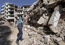 "A Syrian covers his face as he walks with a friend between destroyed buildings in the old city of Homs, Syria, Friday, Feb. 26, 2016. The U.N. Security Council is expected to vote Friday afternoon on a draft resolution endorsing the ""cessation of hostilities"" in Syria that is set to start at midnight local time. The draft, obtained by The Associated Press, also urges the U.N. secretary-general to resume Syria peace talks ""as soon as possible."" (AP Photo/Hassan Ammar)"