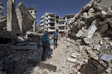 """Syrian children walk between destroyed buildings in the old city of Homs, Syria, Friday, Feb. 26, 2016. The U.N. Security Council is expected to vote Friday afternoon on a draft resolution endorsing the """"cessation of hostilities"""" in Syria that is set to start at midnight local time. The draft, obtained by The Associated Press, also urges the U.N. secretary-general to resume Syria peace talks """"as soon as possible.""""(AP Photo/Hassan Ammar)"""