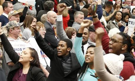 Protesters are escorted out of a rally for Republican presidential candidate, Donald Trump at Radford University in Radford, Va., Monday, Feb. 29, 2016. (AP Photo/Steve Helber)