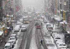 Snow falls on pedestrians and traffic making their way across East Broadway in Lower Manhattan, Saturday, Jan. 7, 2017. The Weather Service issued a winter weather advisory for New York City and the northern suburbs. Snow began falling from New York City and points east at mid-morning Saturday. (AP Photo/Mary Altaffer)