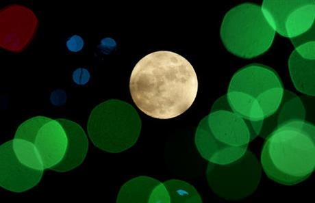 FILE - In this Thursday, Dec. 24, 2015, file photo, a nearly-full moon is seen among Christmas lights at a holiday display near Lenexa, Kan. Israeli scientists reported Monday, Jan. 9, 2017, that rather than one giant impact that knocked off part of early Earth and created the moon, a number of smaller collisions may have produced lots of mini-moons. And those mini-moons, over millions of years, may have clumped together to make one large one. (AP Photo/Charlie Riedel, File)