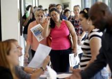 FILE - In this Tuesday, July 19, 2016, file photo, Reina Borges, left, stands in line to apply for a job with Aldi at a job fair in Miami Lakes, Fla. On Friday, Feb. 3, 2017, the Labor Department issues its jobs report for January. (AP Photo/Lynne Sladky, File