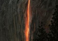 """FILE - In this Feb. 16, 2010, file photo, a shaft of sunlight creates a glow near Horsetail Fall, in Yosemite National Park, Calif. Mother Nature is again putting on a show at California's Yosemite National Park, where every February the setting sun draws a narrow sliver on a waterfall to make it glow like a cascade of molten lava. The phenomenon known as """"firefall"""" draws scores of photographers to the spot, which flows down the granite face of the park's famed rock formation, El Capitan. (Eric Paul Zamora/The Fresno Bee via AP, File)"""