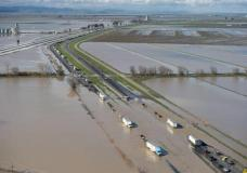 In this view looking north, flood water crosses over Interstate 5 at Williams backing up traffic in both north and southbound lanes for hours on Saturday, February 18, 2017 in Williams, Calif. Northern California and the San Francisco Bay Area were facing a weekend return of heavy rain and winds that lashed them earlier in the week before the storm moves out. (Randy Pench/The Sacramento Bee via AP)