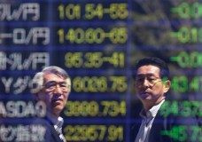 Tokyo businessmen are reflected in an electronic board showing exchange rates between (from top row to third row) the Japanese yen against the U.S. dollar, the euro, Australian dollar and (fourth row to bottom row) indices of Dow Jones, the NASDAQ and Hang Seng Index, outside a brokerage in Tokyo April 14, 2014. Asian share markets gave up more ground in early trade on Monday after a dismal week on Wall Street, helping underpin the safe-haven yen. REUTERS/Issei Kato (JAPAN - Tags: BUSINESS)