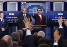 Treasury Secretary Steven Mnuchin, right, joined by National Economic Director Gary Cohn, center, and White House press secretary Sean Spicer speaks in the briefing room of the White House in Washington, Wednesday, April 26, 2017. President Donald Trump is proposing dramatically reducing the taxes paid by corporations big and small in an overhaul his administration says will spur economic growth and bring jobs and prosperity to the middle class. (AP Photo/Carolyn Kaster)