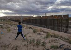 FILE - In this March 29, 2017, file photo, a youth looks at a new, taller fence being built along U.S.-Mexico border, replacing the shorter, gray metal fence in front of it, in the Anapra neighborhood of Ciudad Juarez, Mexico, across the border from Sunland Park, New Mexico. Most Americans oppose funding President Donald Trump's wall along the U.S.-Mexico border. That's according to a poll released Thursday by The Associated Press-NORC Center for Public Affairs Research. (AP Photo/Rodrigo Abd, File)