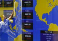 A screen shows the world stock index with the reflection of a worker cleaning a window at the Hong Kong Stock Exchange, Friday, May 5, 2017. Oil prices stabilized in Asian trading Friday after hitting a five-month low while regional stock benchmarks headed lower in holiday-thinned trading. (AP Photo/Kin Cheung)