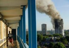 A resident in a nearby building watches smoke rise from a building on fire in London, Wednesday, June 14, 2017. A massive fire raced through the 27-story high-rise apartment building in west London early Wednesday, sending at least 30 people to hospitals, emergency officials said. (AP Photo/Matt Dunham)