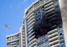 A Honolulu Fire Department helicopter flies near a fire burning on a floor at the Marco Polo apartment complex, Friday, July 14, 2107, in Honolulu. (AP Photo/Marco Garcia)