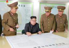 """This image made from video of an Aug. 14, 2017, still image broadcast in a news bulletin on Tuesday, Aug. 15, 2017, by North Korea's KRT shows North Korean leader Kim Jong Un receiving a briefing in Pyongyang. North Korea said leader Kim Jong Un was briefed on his military's plans to launch missiles in waters near Guam days after the Korean People's Army announced its preparing to create """"enveloping fire"""" near the U.S. military hub in the Pacific. Independent journalists were not given access to cover the event depicted in this photo. (KRT via AP Video)"""