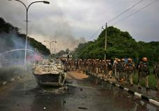 Policemen patrol past a vehicle vandalized by Dera Sacha Sauda sect members near in Panchkula, India, Friday, Aug. 25, 2017.  Deadly riots have broken out in a north Indian town after a court convicted the sect's guru of raping two of his followers. Mobs also attacked journalists and set fire to government buildings and railway stations. (AP Photo/Altaf Qadri)