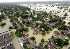 Water from Addicks Reservoir flows into neighborhoods as floodwaters from Tropical Storm Harvey rise Tuesday, Aug. 29, 2017, in Houston. (AP Photo/David J. Phillip)