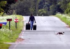 Dulne Brutus, of Haiti, tows his luggage down Roxham Road in Champlain, N.Y., while heading to an unofficial border station across from Saint-Bernard-de-Lacolle, Quebec, Monday, Aug. 7, 2017. Officials on both sides of the border first began to notice last fall, around the time of the U.S. presidential election, that more people were crossing at Roxham Road. Since then the numbers have continued to climb. (AP Photo/Charles Krupa)
