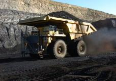 FILE - In this Nov. 15, 2016, file photo, a haul truck with a 250-ton capacity carries coal from the Spring Creek strip mine near Decker, Mont. As President Donald Trump touts new oil pipelines and pledges to revive the nation's struggling coal mines, federal scientists are warning that burning fossil fuels is already driving a steep increase in the United States of heat waves, droughts and floods. (AP Photo/Matthew Brown, File)