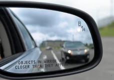 FILE - In his May 22, 2012 file photo, a side mirror warning signal in a Ford Taurus at an automobile testing area in Oxon Hill, Md. Safety systems to prevent cars from drifting into another lane or warn drivers of vehicles in their blind spots are beginning to live up to their potential to significantly reduce crashes, according to two studies released Wednesday, Aug. 23, 2017.  (AP Photo/Susan Walsh, File)