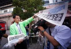 A man distributes an extra edition of a newspaper reporting about North Korea's missile launch, at Shimbashi Station in Tokyo, Friday, Sept. 15, 2017. South Korea's military said North Korea fired an unidentified missile Friday from its capital Pyongyang that flew over Japan before landing in the northern Pacific Ocean. (AP Photo/Eugene Hoshiko)