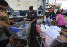 A municipal government worker fills containers with drinking water for residents outside the Juan Ramon Loubriel stadium in the wake of Hurricane Maria in Bayamon, Puerto Rico, Thursday, Sept. 28, 2017. The aftermath of the powerful storm has resulted in a near-total shutdown of the U.S. territory's economy that could last for weeks and has many people running seriously low on cash and worrying that it will become even harder to survive on this storm-ravaged island. (AP Photo/Carlos Giusti)