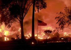 An American flag still fly's as as structures burn in Coffey Park, Monday Oct. 9, 2017. More than a dozen wildfires whipped by powerful winds been burning though California wine country. The flames have destroyed at least 1,500 homes and businesses and sent thousands of people fleeing. (Kent Porter/The Press Democrat via AP)