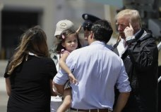 President Donald Trump talks with Governor Ricardo Rosselló, center, carrying his daughter in his arms after his arrival at the Luis Muñiz Air National Guard Base in San Juan, Puerto Rico, Tuesday, Oct. 3, 2017. Trump is visiting Puerto Rico in the wake of Hurricane Maria.(AP Photo/Evan Vucci)
