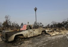 A flag is draped on the back of a truck destroyed by fires in Santa Rosa, Calif., Wednesday, Oct. 11, 2017. Wildfires tearing through California's wine country continued to expand Wednesday, destroying hundreds more homes and structures and prompting new evacuation orders. (AP Photo/Jeff Chiu)