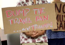 FILE- In this June 30, 2017, file photo, critics of President Donald Trump's travel ban hold signs during a news conference in Honolulu. On Tuesday, Oct. 17, 2017 a federal judge in Hawaii blocked the Trump administration from enforcing its latest travel ban, just hours before it was set to take effect. U.S. District Judge Derrick Watson granted Hawaii's request to temporarily block the policy from taking effect Wednesday. (AP Photo/Caleb Jones, File)