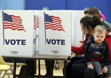 Karina Smith holds her son Kyler Smith, 2, as she fills out her ballot at a polling place Tuesday, Nov. 7, 2017, in Alexandria, Va. Republican candidate for Virginia governor Ed Gillespie faces Democrat Lt. Gov. Ralph Northam in Tuesday's election. (AP Photo/Alex Brandon)