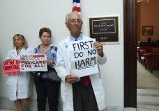 In this July 17, 2017 photo, retired family physician Jay Brock of Fredericksburg, Va., joins other protesters against the Republican health care bill outside the office of Senate Majority Leader Mitch McConnell of Ky., on Capitol Hill in Washington. A year after a big change in leadership, a survey by The Associated Press-NORC Center for Public Affairs Research finds that 48 percent named health care as a top problem for the country. (AP Photo/Manuel Balce Ceneta)