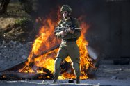 Israeli soldier stands during clashes with Palestinians following a protest against U.S. President Donald Trump's decision to recognize Jerusalem as the capital of Israel in the West Bank City of Nablus, Friday, Dec. 8, 2017. (AP Photo/Majdi Mohammed)