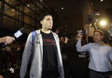 """FILE - In this Nov. 14, 2017, file photo, UCLA basketball player LiAngelo Ball is surrounded by reporters and photographers as he leaves Los Angeles International Airport in Los Angeles. A basketball club from Lithuania says it has signed LiAngelo and LaMelo Ball to pro contracts, making them ineligible for college basketball. The Prienai-Birstonas Vytautas club, which plays in the Lithuanian league, says the brothers will report to the club """"in early January,"""" in a website statement. (AP Photo/Jae C. Hong, File)"""