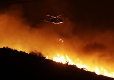A helicopter flies over a wildfire Thursday, Dec. 7, 2017, in Bonsall, Calif. The wind-swept blazes have forced tens of thousands of evacuations and destroyed dozens of homes in Southern California. (AP Photo/Gregory Bull)