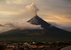 With Legazpi city in foreground, Mayon volcano erupts anew at sunset Thursday, Jan. 25, 2018 in Albay province around 200 miles (340 kilometers) southeast of Manila, Philippines. The Philippine Institute of Volcanology and Seismology said lava flows had advanced more than a kilometer (0.6 miles) and superheated gas and volcanic debris known as pyroclastic flows had reached 5 kilometers (3 miles) from the crater in one area. Mayon's lava fountaining has flowed up to 3 kilometers (1.86 miles) from the crater in a dazzling but increasingly dangerous eruption. (AP Photo/Bullit Marquez)