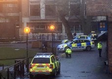 In this photo provided by Solent News & Photo Agency and taken on Sunday, March 4, 2018, a police officer without any protective gear crouches down next to the bench in the Maltings Shopping centre, where Sergei Skripal and his daughter Yulia were found in Salisbury, England. Skripal and his daughter are in critical but stable condition at a hospital in Salisbury. A police officer who came to their aid is in a serious condition, though he is conscious and talking. He was identified Thursday as Sgt. Nick Bailey.(Thomas Belk/Solent News & Photo Agency via AP)