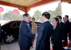 """In this March 26, 2018, photo provided March 28, 2018, by the North Korean government, North Korean leader Kim Jong Un, left, and his wife Ri Sol Ju, rear right, are greeted on arrival at Diaoyutai State Guesthouse in Beijing. North Korea's leader Kim and his Chinese counterpart Xi sought to portray strong ties between the long-time allies despite a recent chill as both countries on Wednesday, March 28, 2018, confirmed Kim's secret trip to Beijing this week. The content of this image is as provided and cannot be independently verified. Korean language watermark on image as provided by source reads: """"KCNA"""" which is the abbreviation for Korean Central News Agency. (Korean Central News Agency/Korea News Service via AP)"""