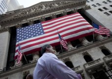 FILE - In this Aug. 8, 2011 file photo, a pedestrian walks past the New York Stock Exchange in New York. The U.S. stock market opens at 9:30 a.m. EST on Friday, March 2, 2018. (AP Photo/Jin Lee, File)