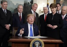 President Donald Trump signs a presidential memorandum imposing tariffs and investment restrictions on China in the Diplomatic Reception Room of the White House, Thursday, March 22, 2018, in Washington. (AP Photo/Evan Vucci)