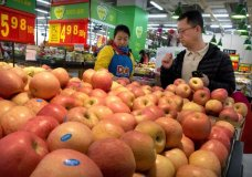FILE - In this March 23, 2018, file photo, a woman wearing a uniform with the logo of an American produce company helps a customer shop for apples a supermarket in Beijing. China raised import duties on a $3 billion list of U.S. pork, fruit and other products Monday, April 2, 2018 in an escalating tariff dispute with President Donald Trump that companies worry might depress global commerce. (AP Photo/Mark Schiefelbein, FILE)