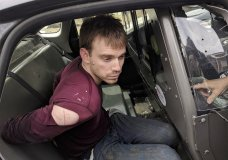 In this photo released by the Metro Nashville Police Department, Travis Reinking sits in a police car after being arrested in Nashville, Tenn., on Monday, April 23, 2018. Police said Reinking opened fire at a Waffle House early Sunday, killing at least four people. (Metro Nashville Police Department via AP)