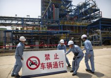 """Workers move a sign near facilities for producing polypropylene at the Sinopec Yanshan Petrochemical Company on the outskirts of Beijing, Friday, May 25, 2018. The facility, part of the Chinese state-owned oil giant Sinopec, opened its doors to journalists on Friday as the U.S. and China continue talks aimed at averting a trade war between the two countries. The sign reads """"Vehicles strictly forbidden to pass through."""" (AP Photo/Mark Schiefelbein)"""