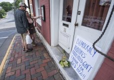 """Passersby examine the menu at the Red Hen Restaurant Saturday, June 23, 2018, in Lexington, Va. White House press secretary Sarah Huckabee Sanders said Saturday in a tweet that she was booted from the Virginia restaurant because she works for President Donald Trump. Sanders said she was told by the owner of The Red Hen that she had to """"leave because I work for @POTUS and I politely left."""" (AP Photo/Daniel Lin)/Daily News-Record via AP)"""