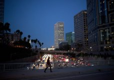 FILE- In this Feb. 14, 2017, file photo, a woman walks on a bridge as heavy traffic moves along the 110 Freeway during rush hour in Los Angeles. From drivers paying more for gas and families bearing heavier child care costs to workers still awaiting decent pay raises to couples struggling to afford a home, people throughout the economy are straining to succeed despite the economy's gains. (AP Photo/Jae C. Hong, File)