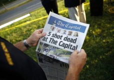 Steve Schuh, county executive of Anne Arundel County, holds a copy of The Capital Gazette near the scene of a shooting at the newspaper's office, Friday, June 29, 2018, in Annapolis, Md. A man armed with smoke grenades and a shotgun attacked journalists in the building Thursday, killing several people before police quickly stormed the building and arrested him, police and witnesses said. (AP Photo/Patrick Semansky)