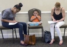 FILE- In this May 15, 2018, file photo, Joan Herrera, center, sits and waits as his mother Andrea Batista Garcia, left, and Marlene Gonzales, fill out job applications while attending the Great Northeast 2018 Job Fair at Capriotti's in McAdoo, near Hazleton, Pa. The U.S. government issues the May jobs report on Friday, June 1. (Ellen F. O'Connell/Hazelton Standard-Speaker via AP, File)